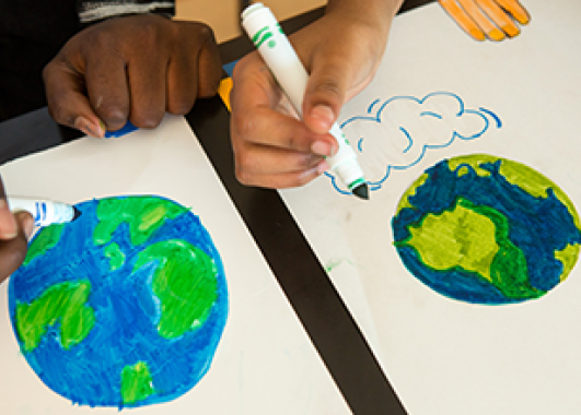 students drawing pictures of Earth with markers.