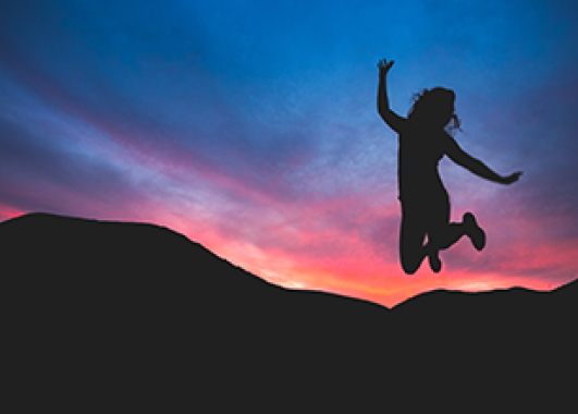 silhouette of girl jumping in the air with a sunset in the background.