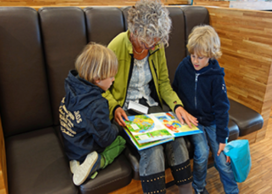 A grey-haired lady reading a book to two young children