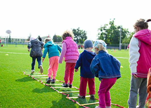 A line of children playing a game outdoors