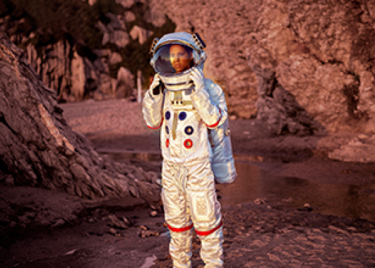 An astronaut standing on a planet that looks like Mars with its red dirt