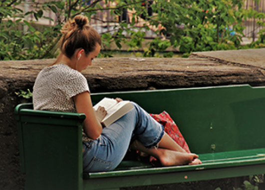 young girl sitting on a bench reading a book.
