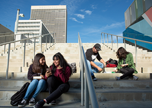 students sitting on a staircase outside in multiple small groups.