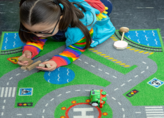 A little girl playing on a rug with roads printed on it