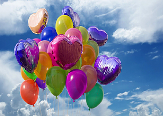 An assortment of balloons floating into the sky
