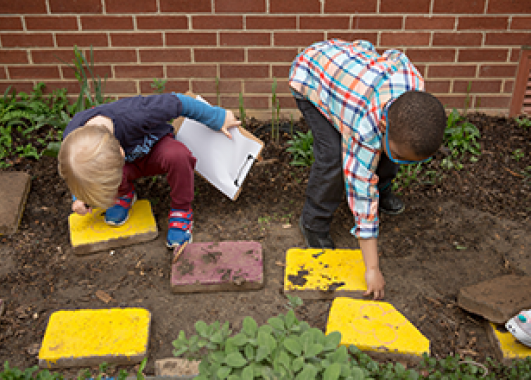 Kids placing red and yellow paving stones in a garden