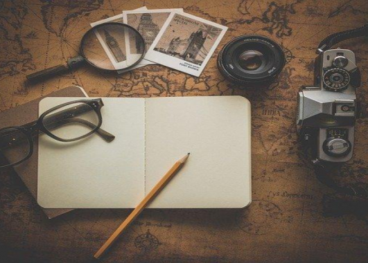 photo of notebook, camera, photos with magnifying glass and glasses scattered on top of a map.