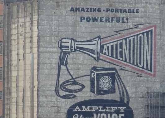 "A building mural in London that reads, ""Amazing. Portable. Powerful. Attention: Amplify your voice!""."