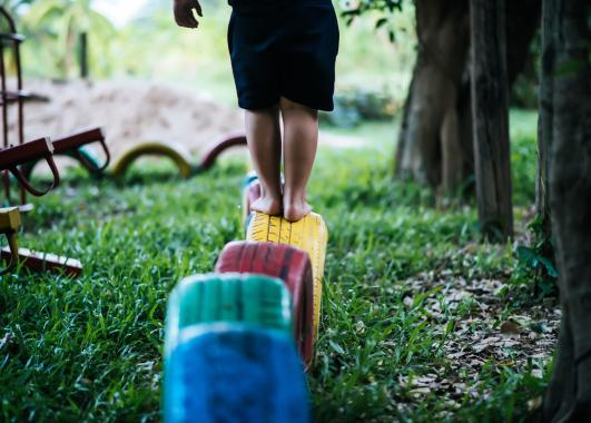 Child standing on a tire that is painted yellow. The yellow tire is 4th in line after a blue, green and red tire.