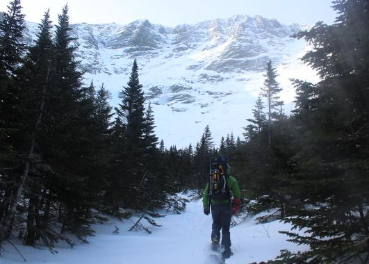 A lone backpacker walks a trail toward a mountain covered in snow.